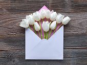 White tulips in blank paper envelope, flat lay on rustic wood