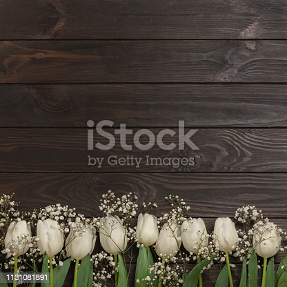 921112244 istock photo White tulips on a brown wooden background. View from above. 1131081891