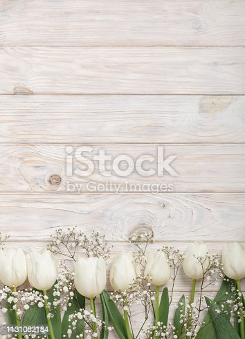 921112244 istock photo White tulips on a light wooden background. View from above. 1131082184