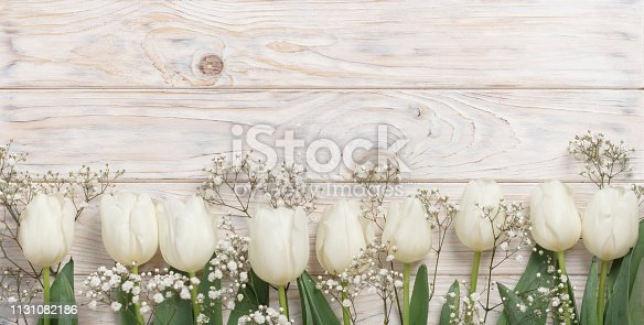 921112244 istock photo White tulips on a light wooden background. View from above. 1131082186