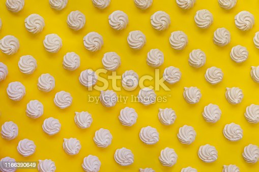 white twisted meringues on yellow background
