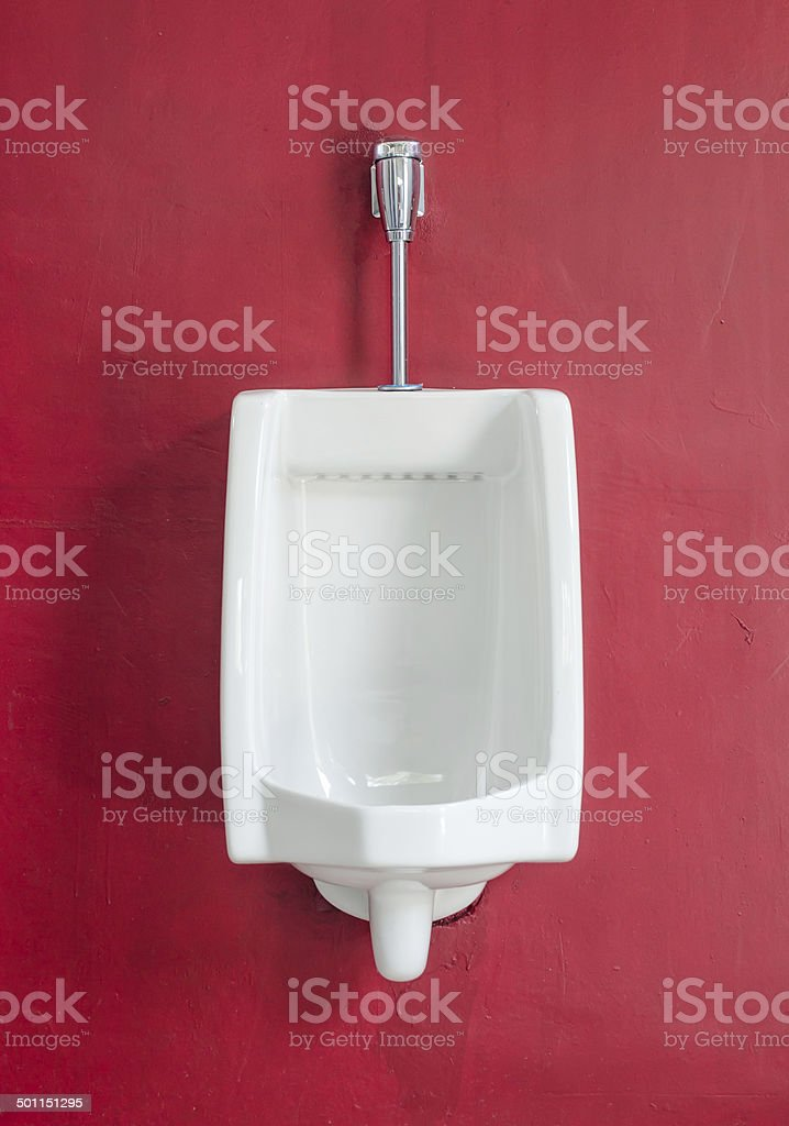 White urinal on red wall stock photo