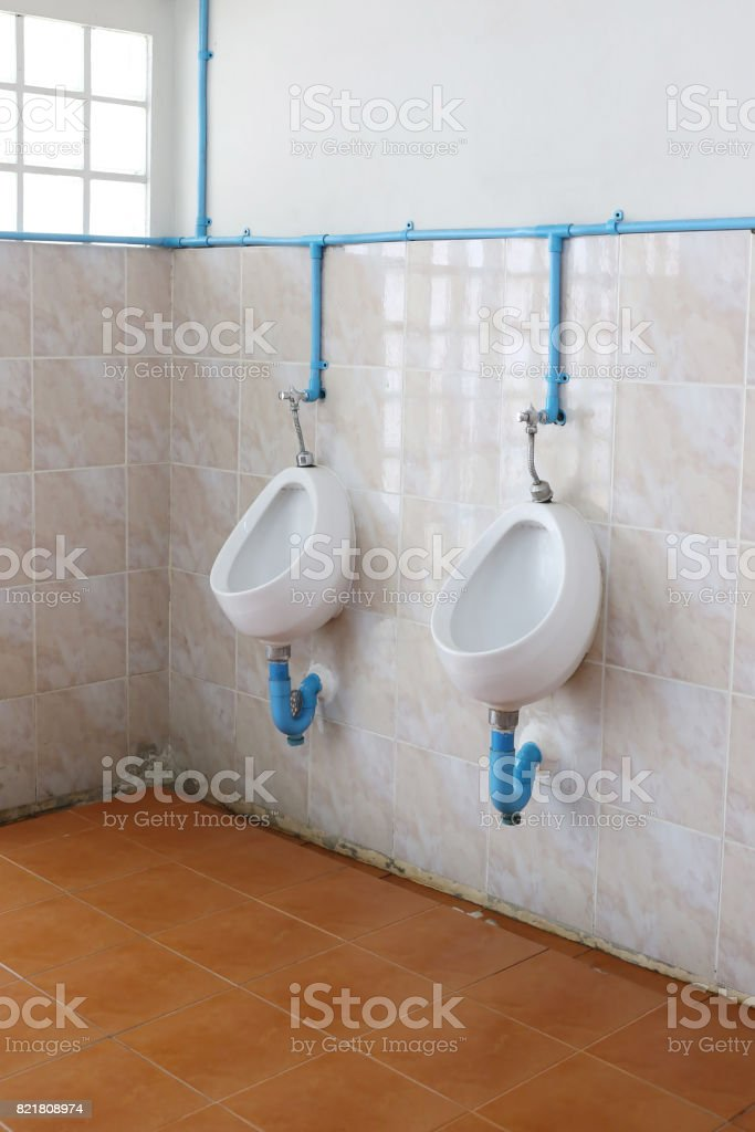 White urinals in public men's bathroom. stock photo