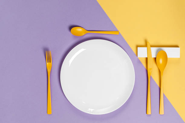 White utensils and yellow cutlery on a pastel colored background. Colors in the style of pop. stock photo