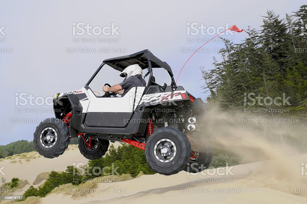 White UTV Side-by-Side Jumps from Sand Dune stock photo