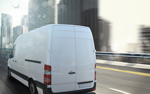White moving van in a city with skyscrapers