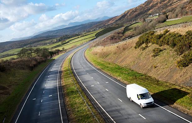 weiße van auf open road in ländlichen umgebung - kastenwagen stock-fotos und bilder