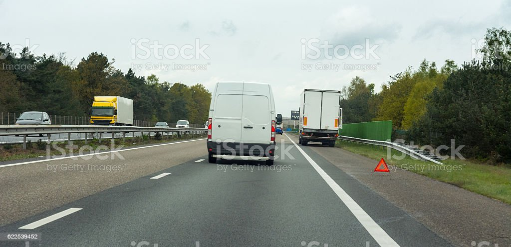 White van passing a warning triangle and  white truck stock photo