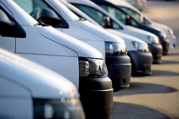 weißen vans in einer reihe - nutzfahrzeug stock-fotos und bilder