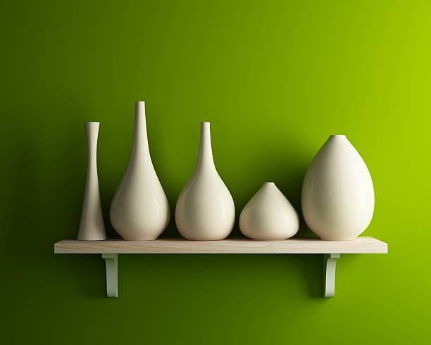 white vase on wood shelf with green wall stock photo