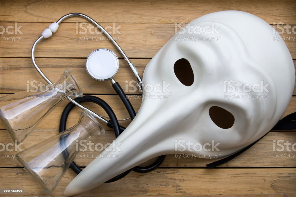 white Venetian mask with mini bottles and stethoscope against wooden background stock photo
