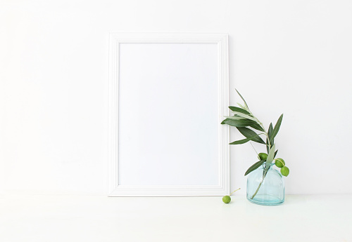 White vertical blank wooden frame mockup with a green olive branches in blue glass vase lying on the table. Mediterranean summer poster product design, styled stock feminine photography. Home decor.