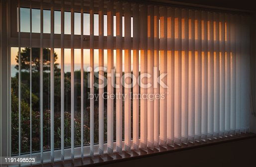 White vertical slat blinds hanging in front of a window as the sun is setting turning the light golden. The slats have sealed glued pockets and no cords at the bottom.