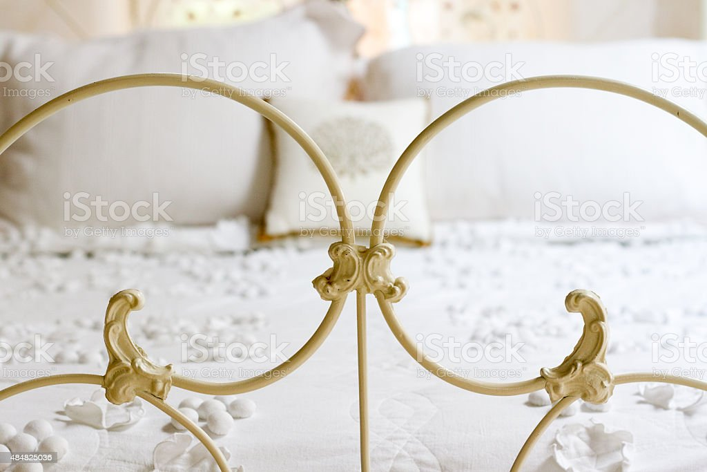 White Victorian Iron Bed with Pretty White Bedspread and Pillows stock photo