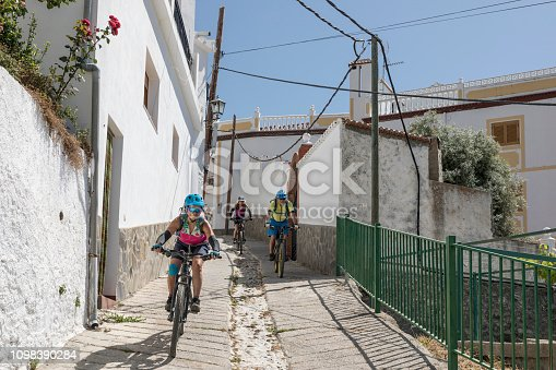 Three adult mountainbikers are riding downhill in a narrow alley of a village in the Andalucian Sierra Nevada which is a mountain range in the province of Granada and, a little further, Málaga and Almería in Spain. It contains the highest point of continental Spain and the third highest in Europe after the Caucasus Mountains and the Alps, Mulhacén at 3,479 metres (11,414 ft) above sea level.  It is a popular tourist destination. Parts of the range have been included in the Sierra Nevada National Park. The range has also been declared a biosphere reserve. Canon EOS 5D Mark IV, 1/500, f/8, 43 mm.