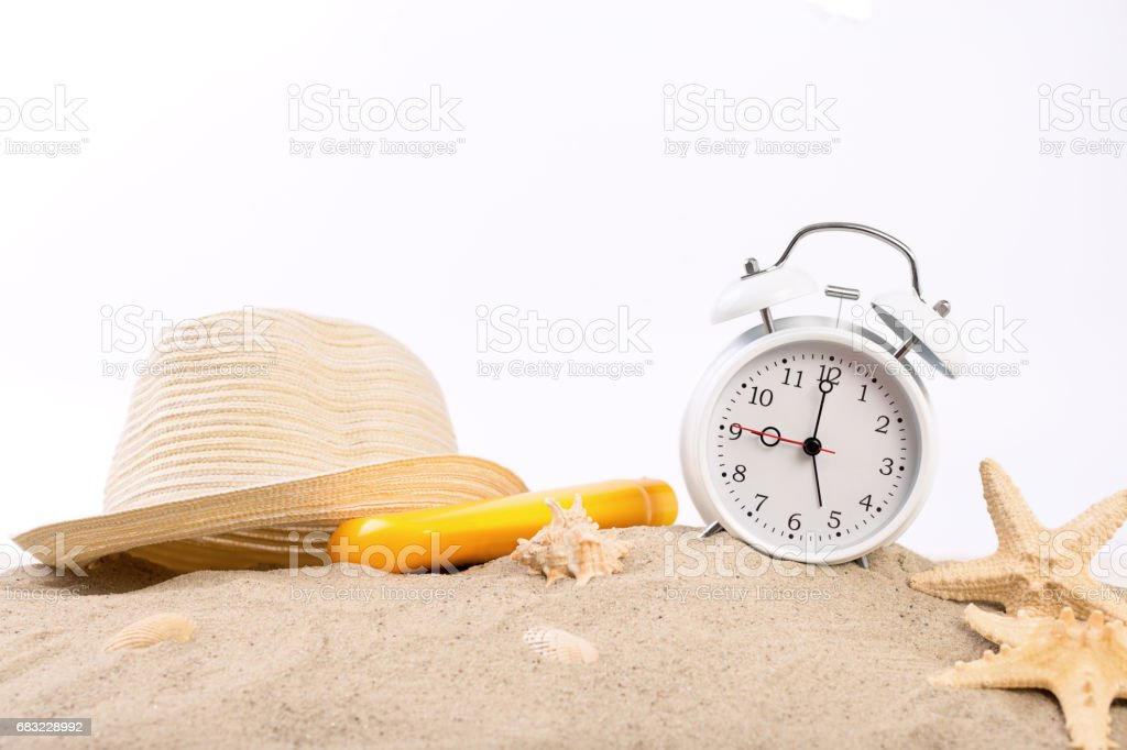 White vintage alarm clock, straw hat, suntan lotion and starfish on the sand royalty-free 스톡 사진
