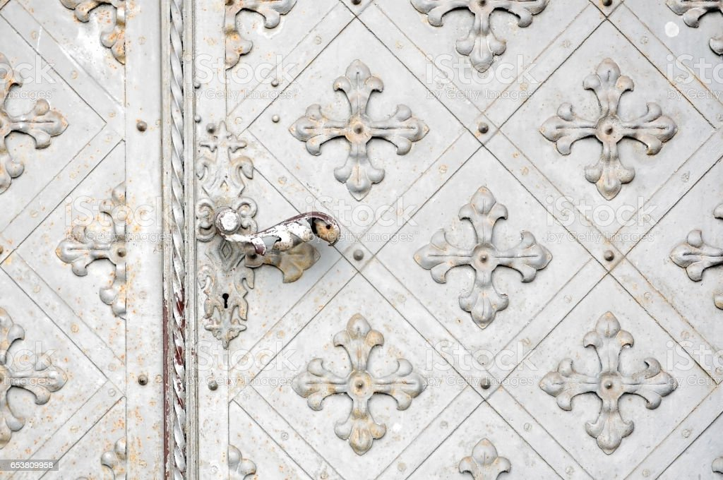 White vintage metallic texture of the crosses. Old gate with the door handle. stock photo