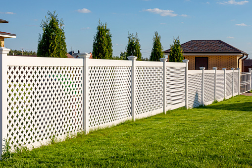 White vinyl fence in a cottage village. Several panels are connected by columns. Tall Thuja bushes behind the fence. Fencing of private property.