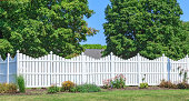 New white vinyl fence with nice yard landscaping and trees in the back ground.