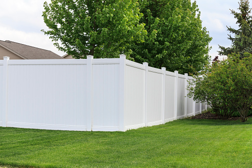 A white vinyl fence running across a yard on spring day with blue sky and trees in the background