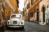 White Volkswagen beetle car parked on the street in Rome. Rome, Italy 05/19/2019