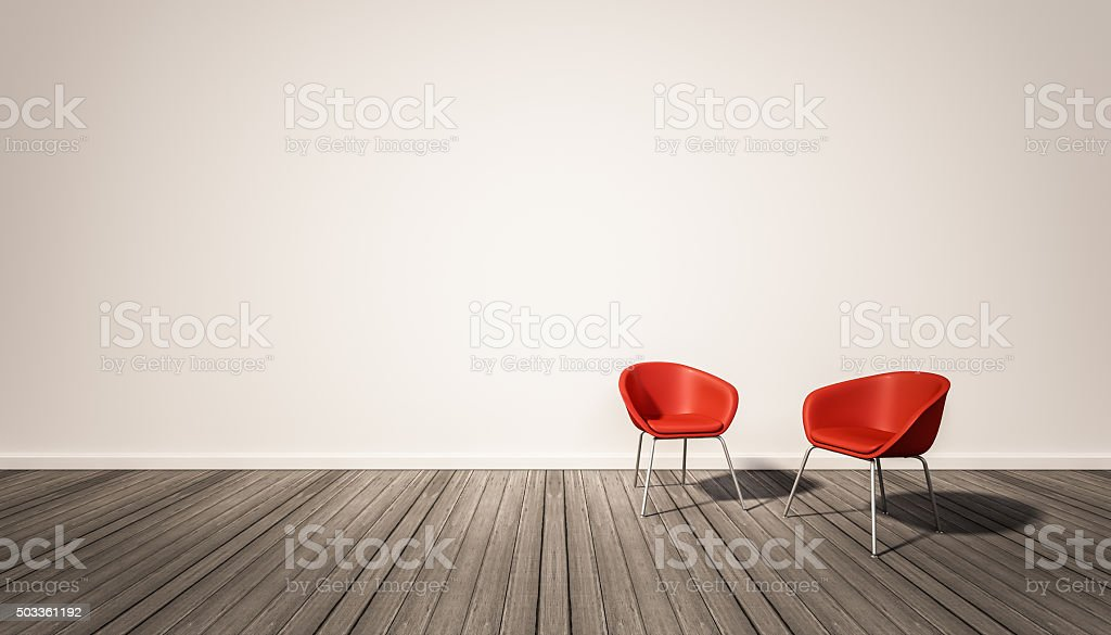 white wall and dark wood floor, with red chairs stock photo