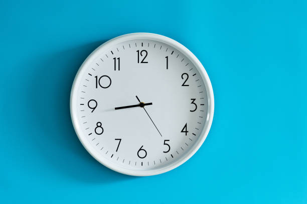 White wall clock on blue background stock photo