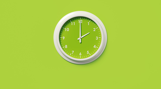 White wall clock on green background. Horizontal composition with copy space.