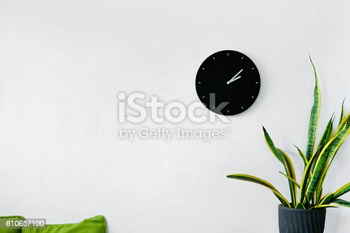 White wall decoration with clock, sofa and plants