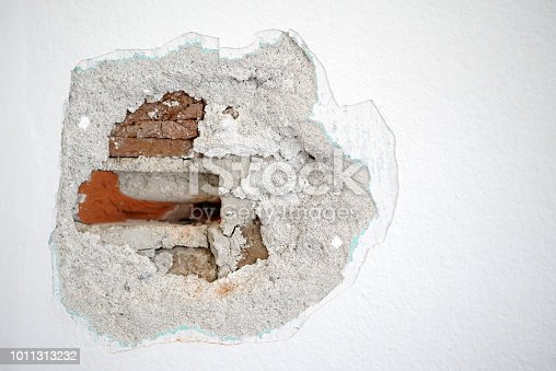 White wall with a hole inside so that damaged bricks are visible.