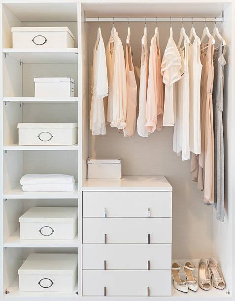 white wardrobe on wooden floor with dress stock photo