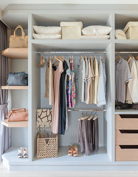 white wardrobe with shirts and pants hanging stock photo