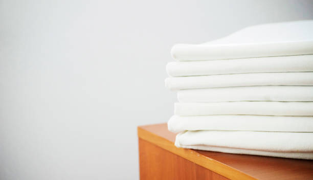 white washed ironed pile of linen on the wooden stock photo