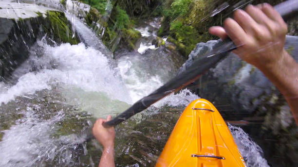 White water kayaker paddles down waterfall stock photo