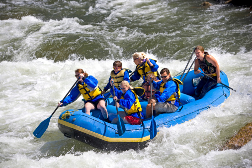 A group of men, women and children, with a guide, white water rafting on the Arkansas River in Colorado.