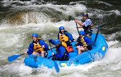 A group of men and women, with a guide, white water rafting on the Arkansas River in Colorado.