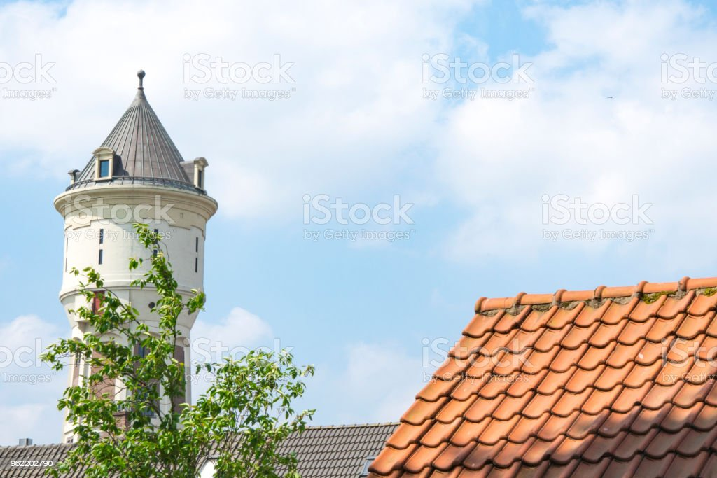 white water tower, orange roof tiles in Roosendaal, The Netherlands, space for text stock photo