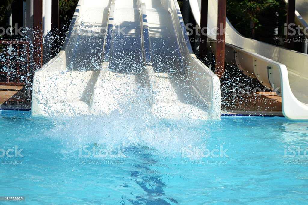 white waterslides at a swimming pool stock photo
