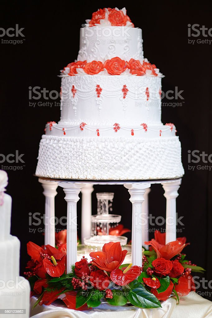 White wedding cake decorated with red flowers stock photo