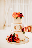 White wedding cake decorated with red roses.