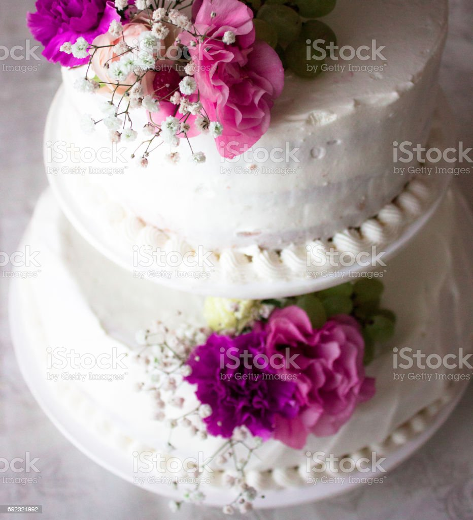 White wedding cake in three tiers with live purple and pink flowers