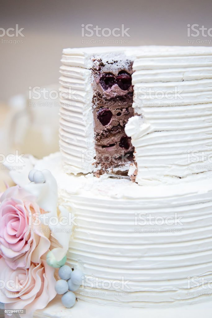 White wedding cake, sliced open, with cholate and black cherry filling