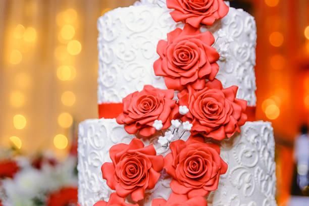 weiße hochzeitstorte mit roten süßigkeiten blüten, nahaufnahme - rosentorte stock-fotos und bilder