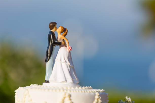 white wedding cake with topper stock photo