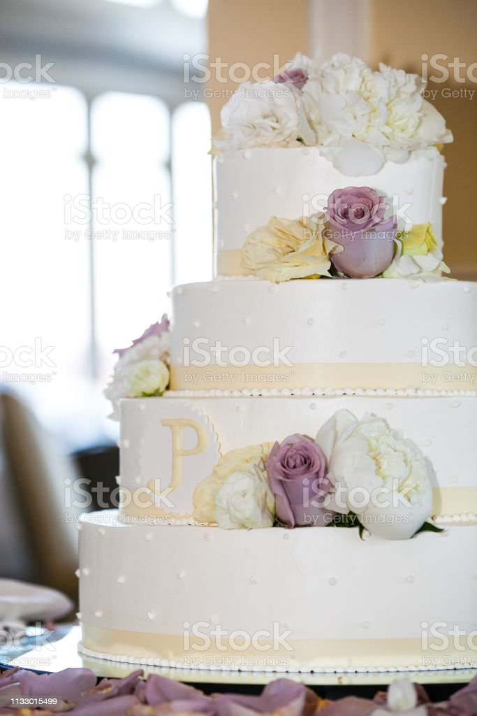 White wedding cake with yellow, white, and purple flowers. 4 tiers -...