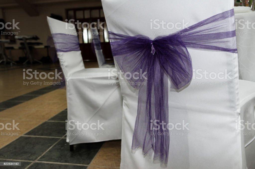 White wedding chairs with purple ribbon stock photo