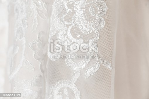 Close up of white lace embroidered with floral flourish pattern for bridal white wedding dress.