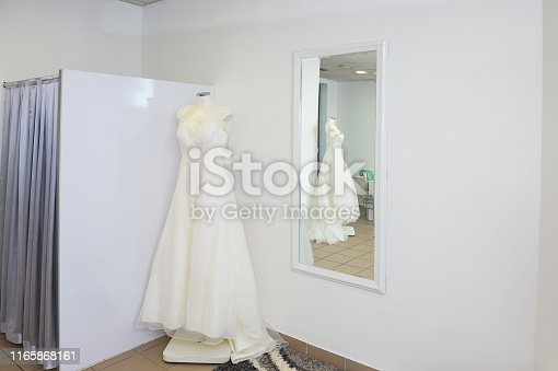 White Wedding Dress on A Stand in Shop With Tag