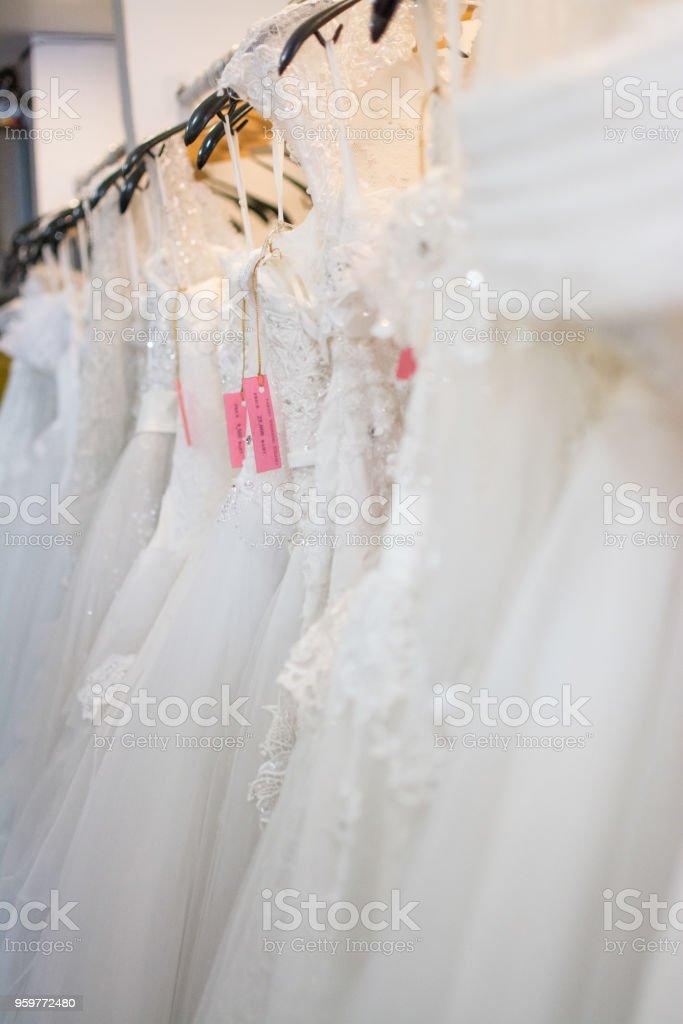 white wedding dresses hanging on racks stock photo
