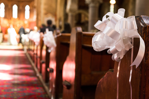 White Wedding ribbon decoration on wooden pew in church